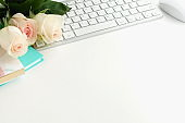 Flat lay women's office desk. Female workspace with laptop,  flowers pink roses,  accessories, notebooks, glasses,  on white background. Top view feminine background.Copy space.