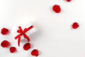 White gift box with red ribbon red velvet rose petals on white background. Flat lay