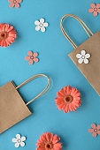 Coral gerbera daisy flowers and craft paper shopping bags on blue paper