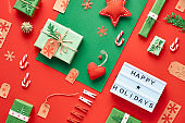 """Red and green Xmas background. Eco friendly zero waste Christmas and New Year decorations. Geometric flat lay with gifts, boxes, coffee mug and textile toys. Light box with text """"Happy Holidays""""."""