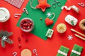 Red and green Xmas background. Trendy eco friendly zero waste Christmas and New Year decorations and gifts. Geometric flat lay with gifts, cranberry, bamboo coffee mug and candy canes.