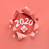 Coral color paper flat lay with snowflakes and ripped hole in the middle, number 2020
