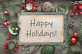 """Rustic Christmas background in green and red with fir twigs. Text """"Happy Holidays"""" on craft paper.Xmas gifts in craft cardboard boxes, decorative berries and trinkets, mint green cord and scissors."""