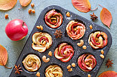 Tray of apple roses baked in puff pastry on gray crackled wood with Autumn leaves