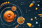 Healthy food concept background. Space pumpkin solar system with carrot, pepper and lentils soup.