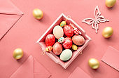 Easter flat lay on coral color paper with wooden tray full of decorative eggs, greeting cards, with envelopes and decorative flowes