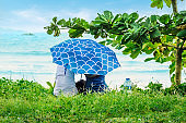 Asian couple locked up with an umbrella and looking at the ocean.