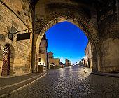 Romantic Prague at dawn, entrance to Charles Bridge through the illuminated arch of Lesser Town Bridge