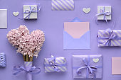 Purple springtime  background with pink hyacinth flowers, wrapped gift boxes and decorative hearts, copy-space