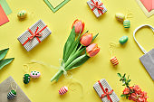 Easter flat lay on yellow paper. Bunch of tulips, gift boxes, decorative eggs and paper bags