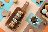 Macarons and expresso, flat lay on geometric paper background with Autumn decorations