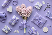 Springtime lilac colored background with pink hyacinth, wrapped gift boxes and decorations