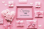 """Pink monochrome Spring  background with pearl hyacinth flowers, wrapped gift boxes and decorative hearts around wooden frame with text """"Spring time is coming""""."""
