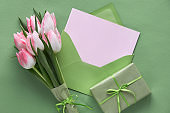 Springtime green background with white and pink tulips and wrapped gifts