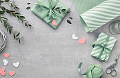 Springtime flat lay with giift boxes, decorative hearts and eucalyprus leaves, text space