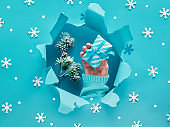 Turquoise paper flat lay with hand holding gift, snowflakes and ripped hole in the middle
