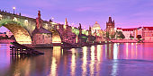 Prague on sunset, panoramic image. Illuminated Charles bridge, Bridge Tower and old buildings on the riverside under purple sky with golden reflections in water