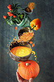 Pumpkin and orange lentil soup and its ingredients, creative background