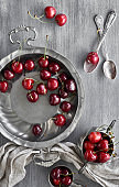 Tasty cherry in vintage metal plates, top view on textured background