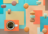 Macaroons and expresso, flat lay on geometric paper background