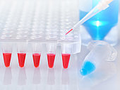 Plastic tube with blue DNA amplification mixture and red tubes with PCR samples