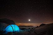Camp site underneath sky full of stars in winter season