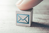 Macro Of An E-Mail Icon On A Wooden Block Arranged By A Female Finger On A Table