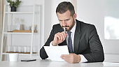 Pensive Businessman Reading Documents in Office, Paperwork