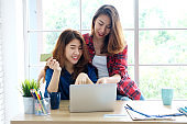 Two young asian women holding credit card and using laptop computer for shopping online, business and technology concept, digital marketing, casual lifestyle