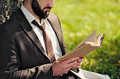 Young attractive bearded business man sitting on green grass under tree and resting in park. Read book, drink coffee. Relaxed, tired of work, lunch break.