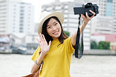 Young asian female traveler taking selfie photo in city outdoors background, Travel blogger, vlog concept