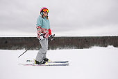 A beautiful young chewing woman in an extreme sports suit, hat and a helmet with a mask on a winter slope is skiing against the background of the forest.