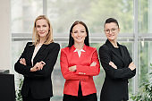 Three young attractive women in business suits posing against the backdrop of a light office. Head and subordinates. Working team of professionals and colleagues.