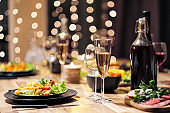 Festive table setting. Food and drinks, plates and glasses. Evening lights and candles. New Year's Eve.