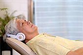 Senior asian man listening headphones whlie laying on sofa in home living room with happiness, retirement lifestyle and technology