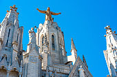 Golden Statue of Jesus Christ on the facade of the Temple of the Sacred Heart of Jesus, Barcelona, Catalonia, Spain. Isolated on blue background