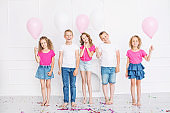 Happy beautiful cute kids smile at the holiday party with balloons and confetti together in the white room