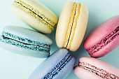 Colorful macarons on turquoise background.