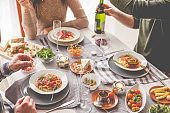 Friends having a pasta dinner at home or at a restaurant
