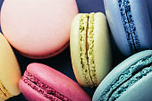 Colorful macarons on dark blue background.