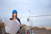 A beautiful young woman civil engineer looks at the camera and holds the plan of the project