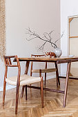 Stylish and beige interior of dining room with design wooden table and chairs, vase with flowers, elegant and rattan accessories. Korean style of home decor. Wooden parquet. Template.