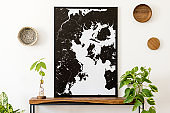Stylish and cozy scandinavian interior of living room with wooden console, rings on the wall, avocado plant and plants. Black mock up poster map. Design home decor. Template. White walls.