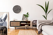 Stylish scandinavian living room interior with gray sofa, black lamp, design commode, tropical plants, sculpture, books and personal accessories. Mock up abstract paintings on the wall. Template.