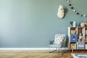Stylish scandinavian newborn baby room with wooden cabinet, toys, children's mint chair, natural basket Modern interior with eucalyptus background walls, wooden parquet and cottona balls. Home decor.