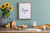 Stylish and sunny interior of kitchen space with wooden table, brown mock up photo frame, breakfast and sunflowers. Scandinavian home decor with kitchen accessories. Template. Eucalyptus color concept