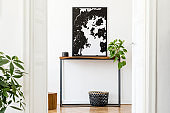 Stylish and cozy scandinavian interior of living room with wooden console, basket, cube, plants and elegant personal accessories. Black mock up poster map. Design home decor. Template.