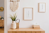 Stylish and modern boho interior of living room with mock up photo frames, flowers in vase, wooden desk, beige macrame and elegant accessories. Design home decor. Bohemian concept. Mockup ready to use