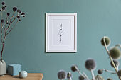 Minimalistic interior design of living room at nice apartment with stylish shelf, vase with flowers, box and elegant accessories. White mock up photo frame. Eucalyptus color concept. Template.