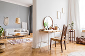 Modern and design home interior of open space with wooden desk, coffee table, sofa, chair, plants, mirror, macrame and elegant accessories. Stylish and minimalistic home decor. Template. Bright rooms.